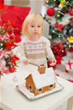 Portrait of baby eating cookies near Christmas Gingerbread house
