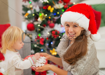 Happy mother giving baby Christmas cookies