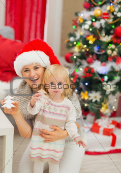 Portrait of smiling mother and baby with Christmas tree cookies