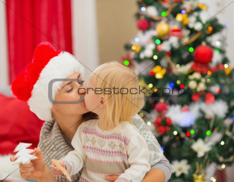 Mother and baby kissing near Christmas tree