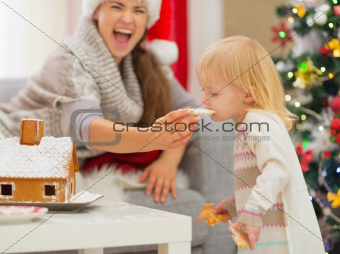 Mother giving bite Christmas cookies to baby
