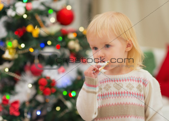 Baby eating Christmas cookies near Christmas tree