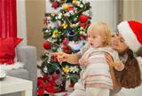 Eat smeared baby and mother near Christmas tree looking on copy space