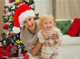 Portrait of laughing mother and eat smeared baby near Christmas tree