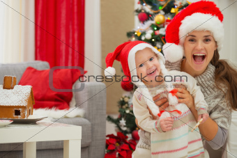 Portrait of mother and eat smeared baby in Christmas hats near Christmas tree