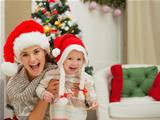 Portrait of mom and eat smeared baby girl in Christmas hats near Christmas tree