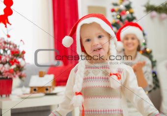 Portrait of eat smeared baby girl in Christmas hats dancing