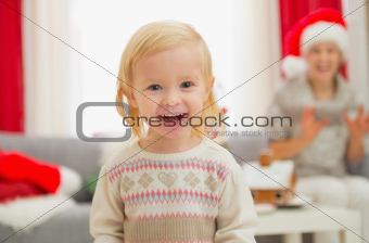 Portrait of eat smeared baby girl in Christmas enjoying Christmas