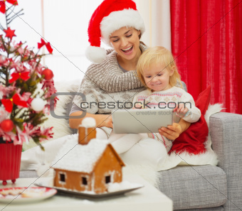 Mother showing baby something in tablet PC near Christmas tree