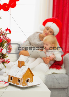 Closeup on Christmas Gingerbread house and mother and baby girl using tablet PC in background