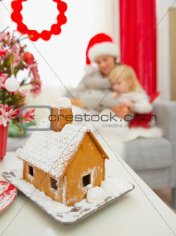 Closeup on Christmas Gingerbread house and mother and baby using tablet PC in background