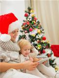 Happy mother and kid using tablet PC near Christmas tree