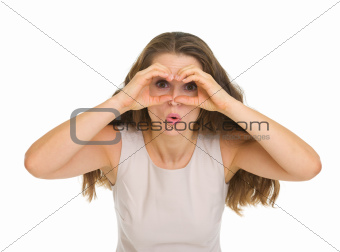 Surprised young woman looking through binoculars shaped hands