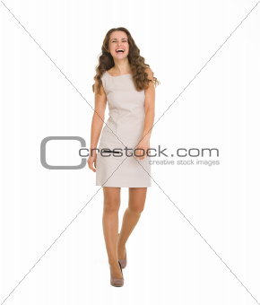 Young woman in dress making step forward