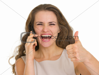 Portrait of happy woman talking mobile and showing thumbs up