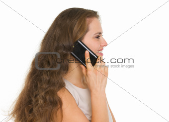 Smiling woman talking mobile phone. Side view