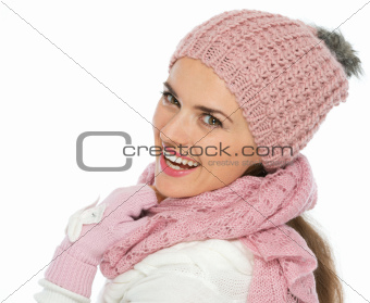 Smiling woman in knit scarf, hat and mittens looking back