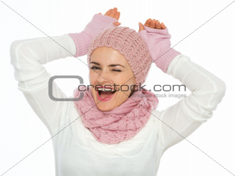 Portrait of playful young woman in knit scarf, hat and mittens