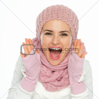 Happy woman in knit winter clothes shouting through megaphone shaped hands