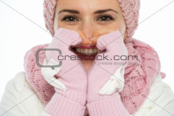 Closeup on young woman smiling through heart shaped hands