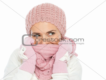 Happy woman in knit winter clothes hiding in scarf and looking on copy space