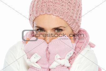 Happy woman in knit winter clothes breathing on hands