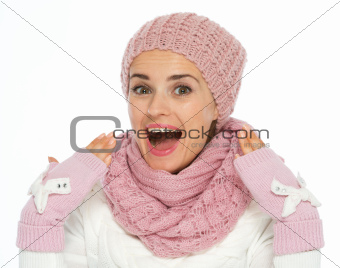 Surprised young woman in knit scarf, hat and mittens