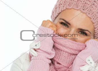 Portrait of woman in knit winter clothing closing face with scarf