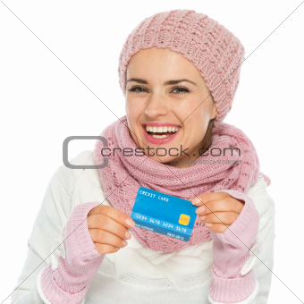 Smiling woman in knit scarf, hat and mittens holding credit card