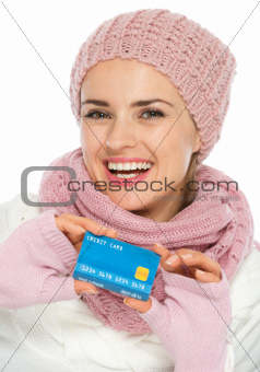 Happy woman in knit winter clothing showing credit card