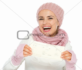 Happy young woman in knit winter clothing holding air ticket