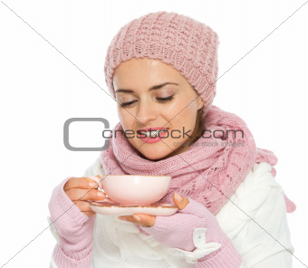 Happy young woman in knit winter clothing enjoying cup of hot tea