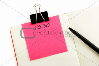 notebook with to-do sticky, pen and clip