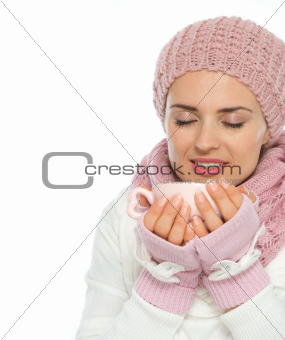 Happy young woman in knit winter clothing enjoying cup of hot coffee
