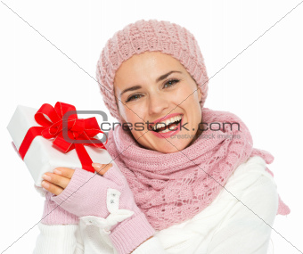 Happy young woman in knit winter clothing holding Christmas present box