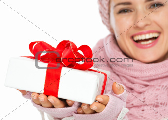 Closeup on Christmas gift box in hand of woman in winter clothing