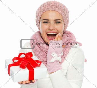 Surprised young woman in knit winter clothing holding Christmas present box