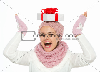 Happy woman in knit winter clothing balancing Christmas present box on head