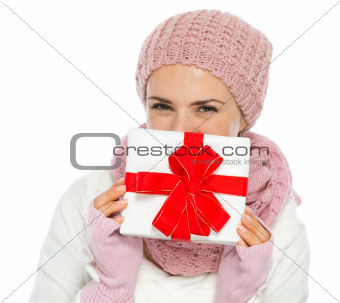 Happy woman in knit winter clothing hiding behind Christmas present box