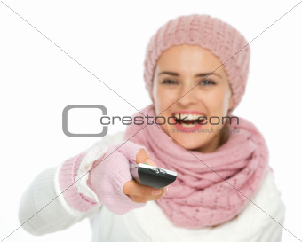 Closeup on TV remote control in hand of happy woman in knit winter clothing