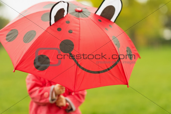 Baby hiding behind red umbrella