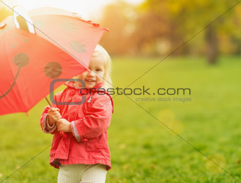 Smiling baby looking out from red umbrella