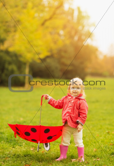 Happy baby holding red umbrella
