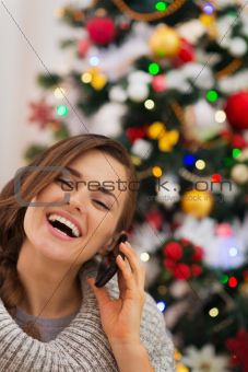 Smiling woman near Christmas tree making phone call