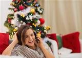 Happy woman near Christmas tree speaking mobile