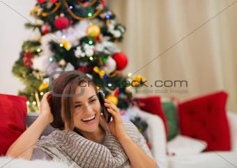 Happy woman near Christmas tree speaking mobile