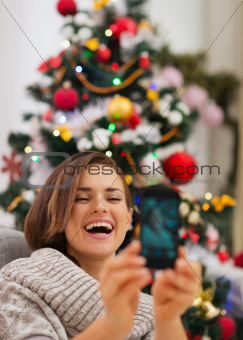 Happy woman near Christmas tree making self photo