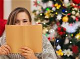 Woman hiding behind book in front of Christmas tree