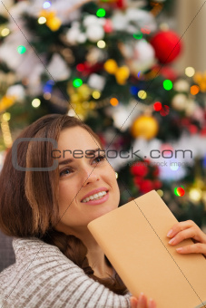 Dreaming woman with book near Christmas tree