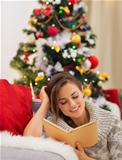 Woman reading book near Christmas tree
